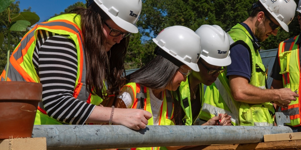 Students and the construction team sign the beam.