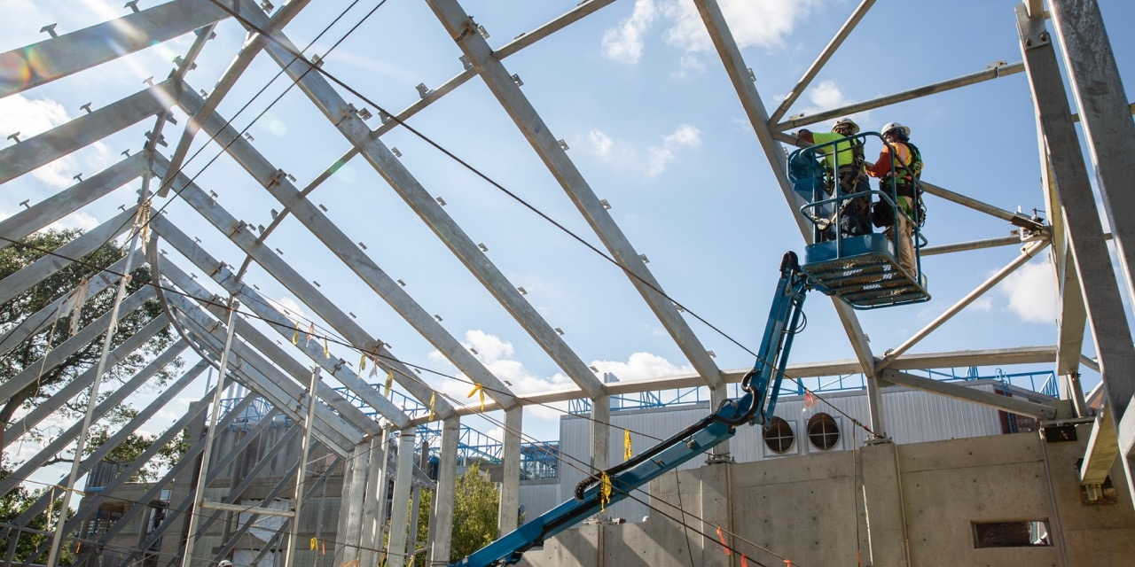 A construction team lifts the final beam into place at the Global Flora greenhouse on Science Hill.