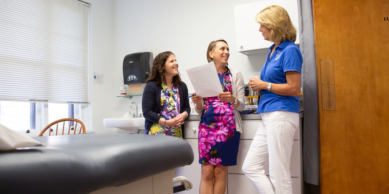 Two new doctors, who are joining the health services team, talk with a nurse.