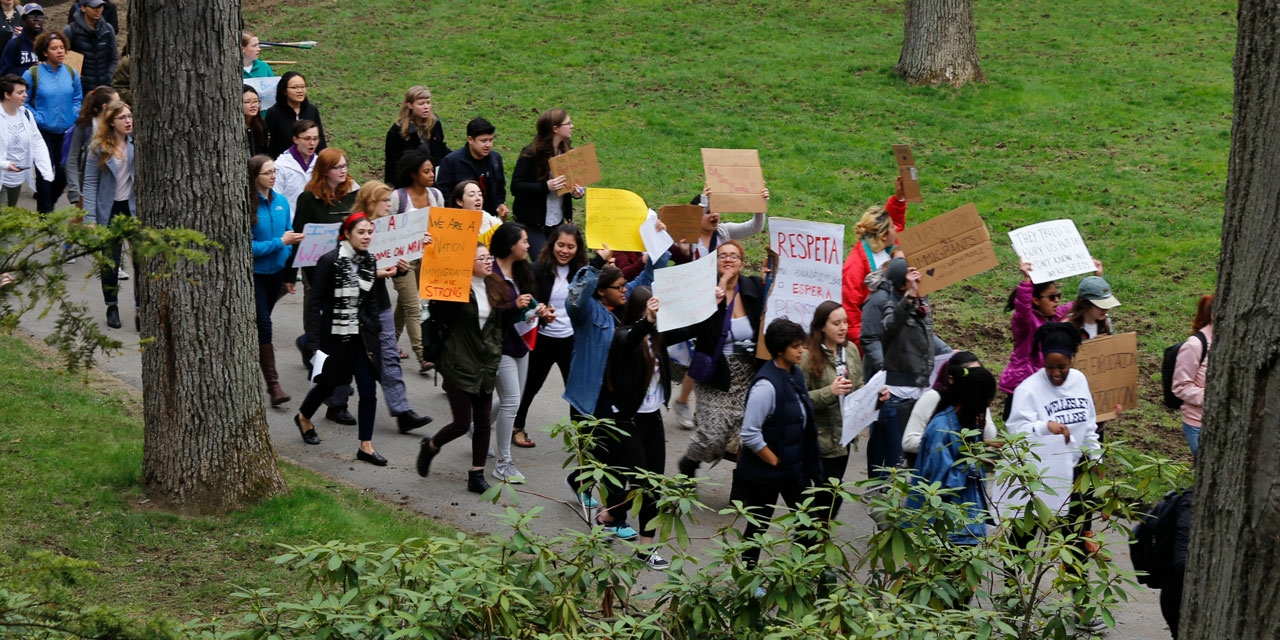 A group of students march outside of Green Hall on May 1, 2017 with signs supporting Immigrant rights