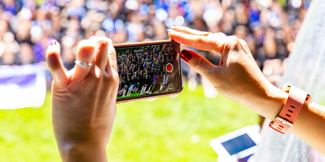A woman takes a video of the seniors lining up for their class photo.