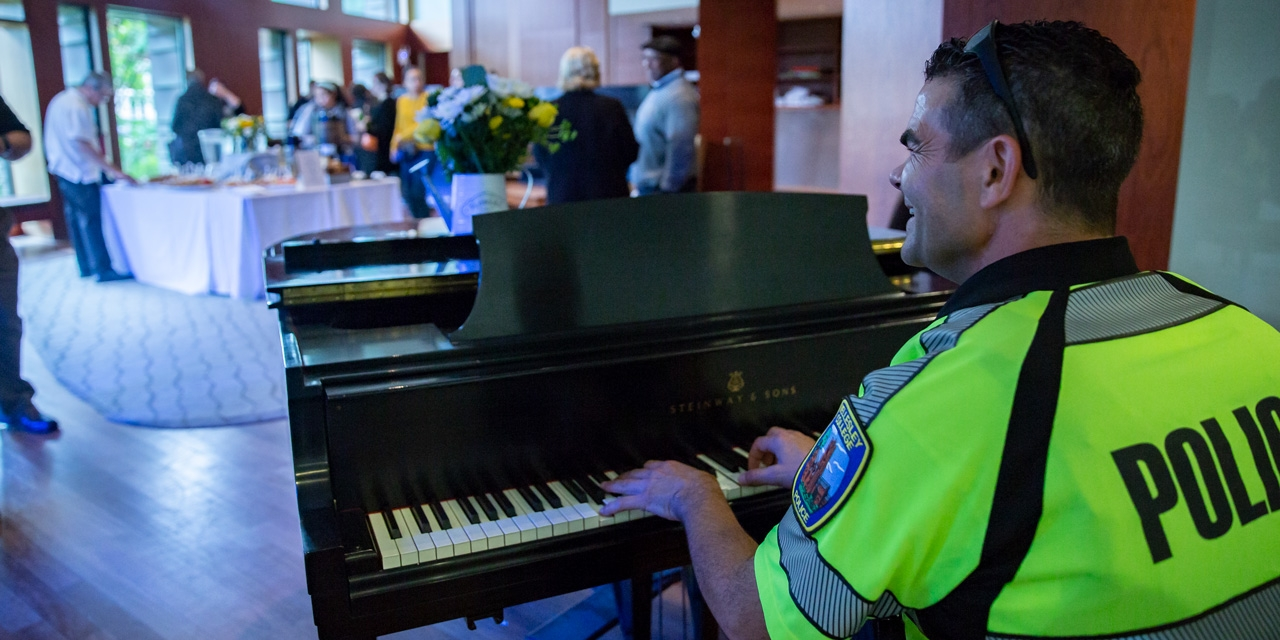 A Wellesley Police Officer plays a piano.