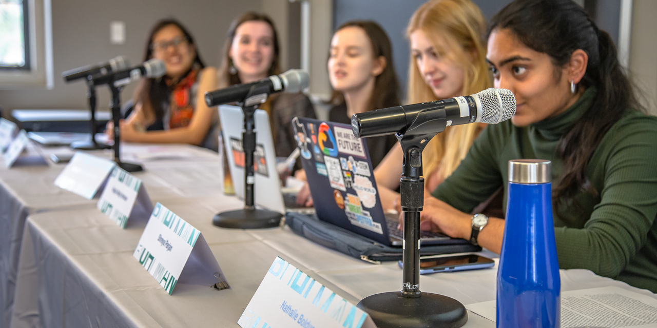 Five students speak into microphones at the beginning of the Ruhlman Conference.