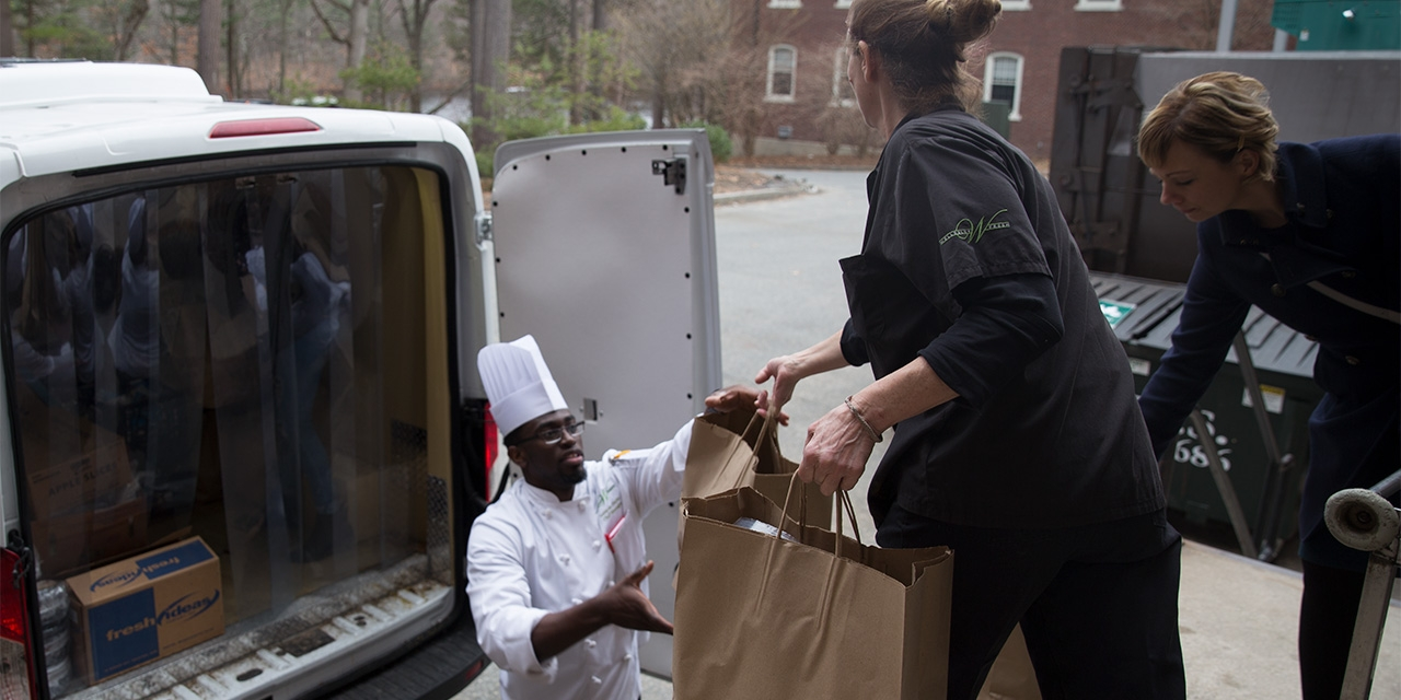 Volunteers load food into the back of a truck from a Wellesley dining hall.