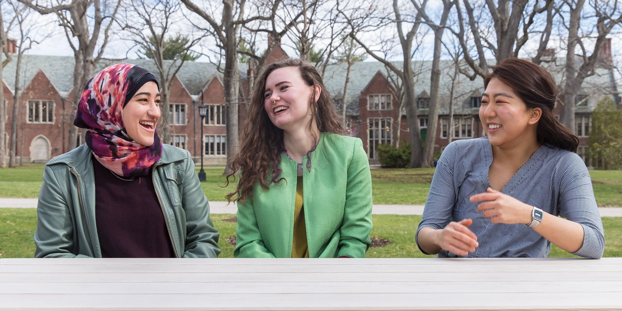 Three student sit in the academic quad in conversation.