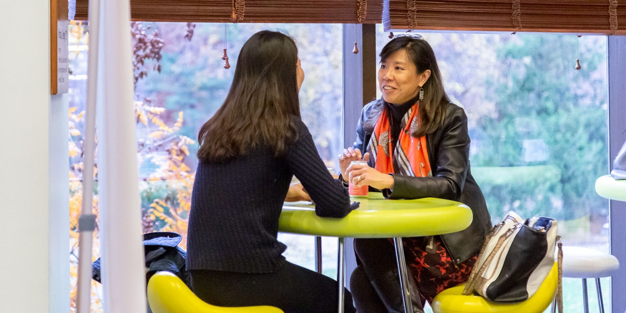 Alumna Staphanie Hsieh sits with a student in Lulu Campus Center