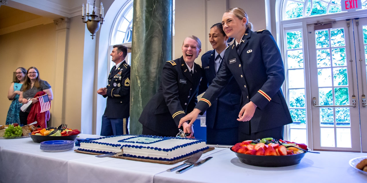 Three ROTC cadets cut a cake with  a saber