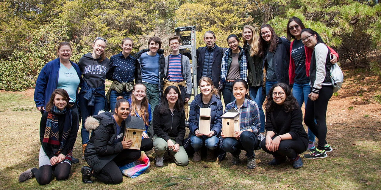 Andrew Mowbray and his students stand in a group photo outside wth their bird boxes.