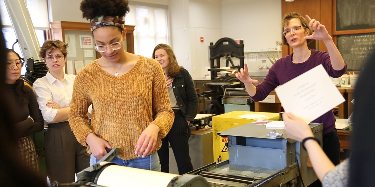 A student uses a printing press while her class and professor look on.
