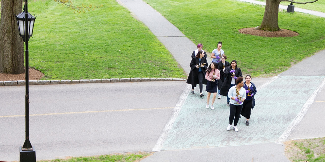 A group of students walk from the science complex to Green Hall holding the microscopes.