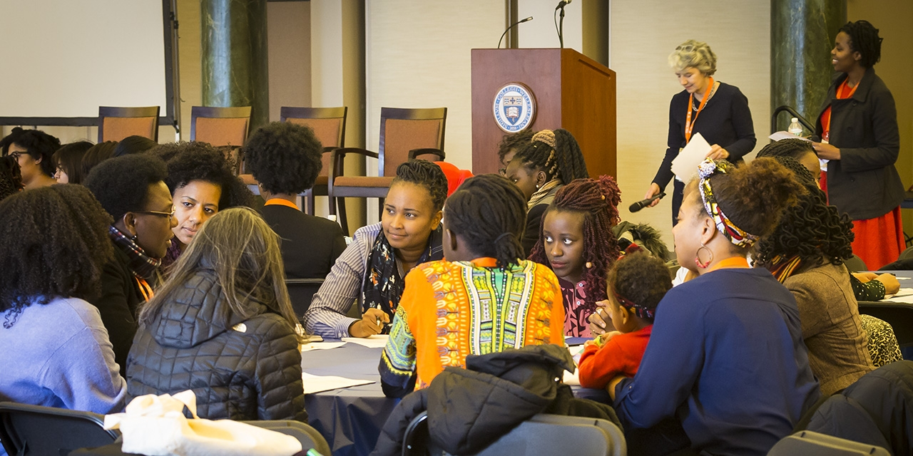 Groups of students sit at tables in deep discussion.