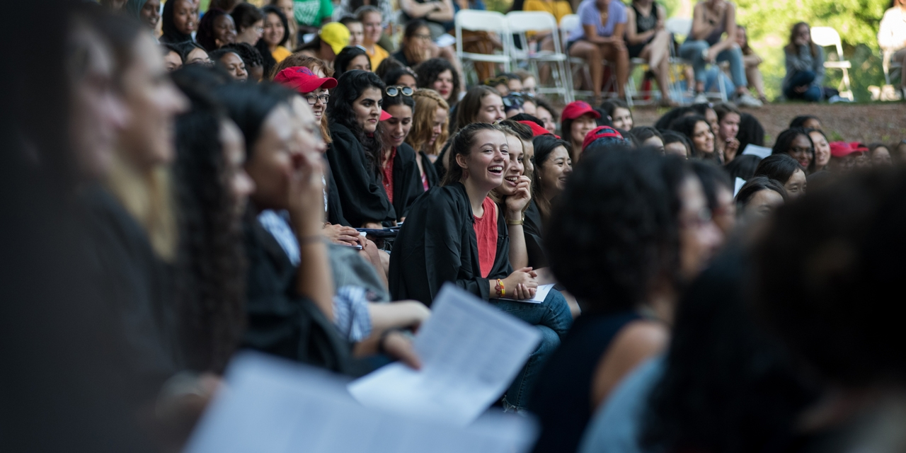 A student laughs amid a crowd of students in the theater.