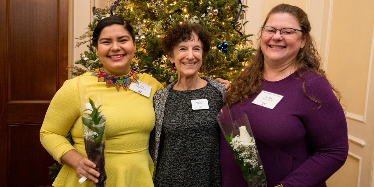 Three women stand in front of a Christmas tree which is decorated in yellow and purple.