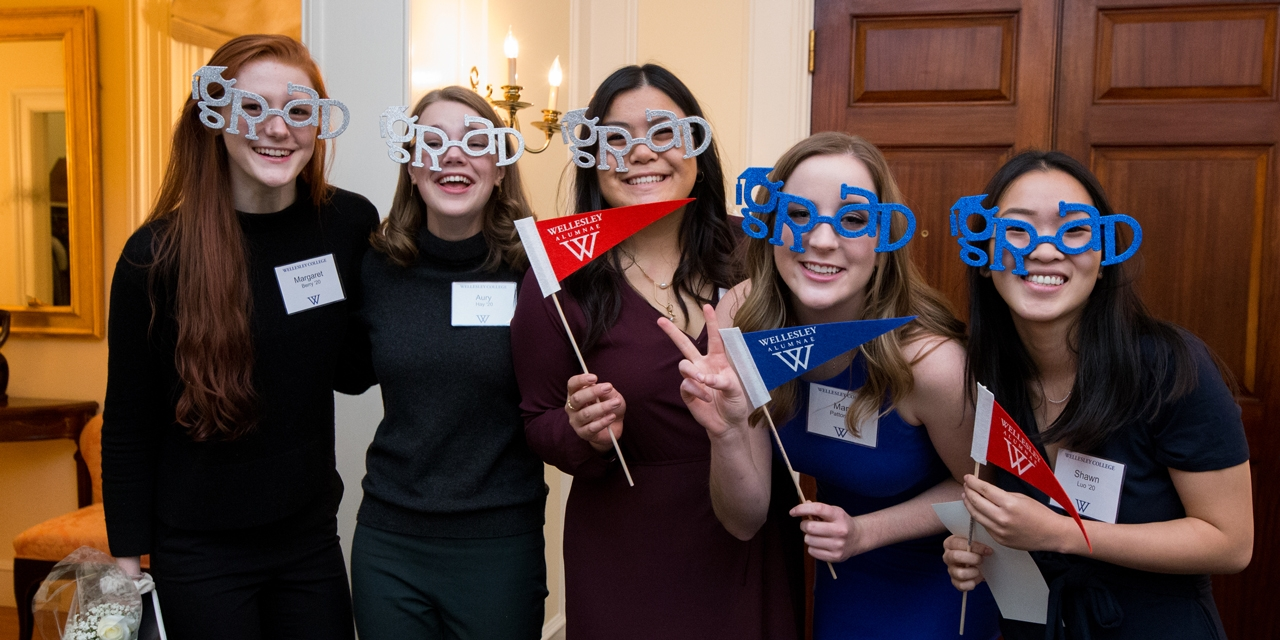"""Five students pose for the camera wearing """"grad glasses"""" and holding Wellesley alumnae pennants"""