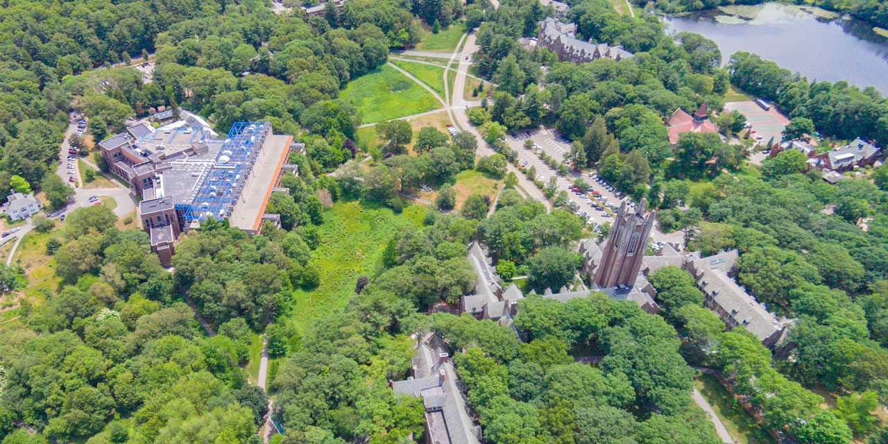 An aerial view of Wellesley's campus featuring lake waban and green hall.