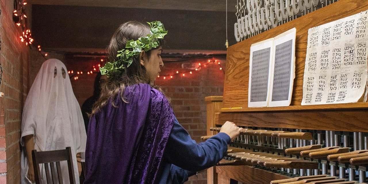 Students dressed in costumes play the carillon.