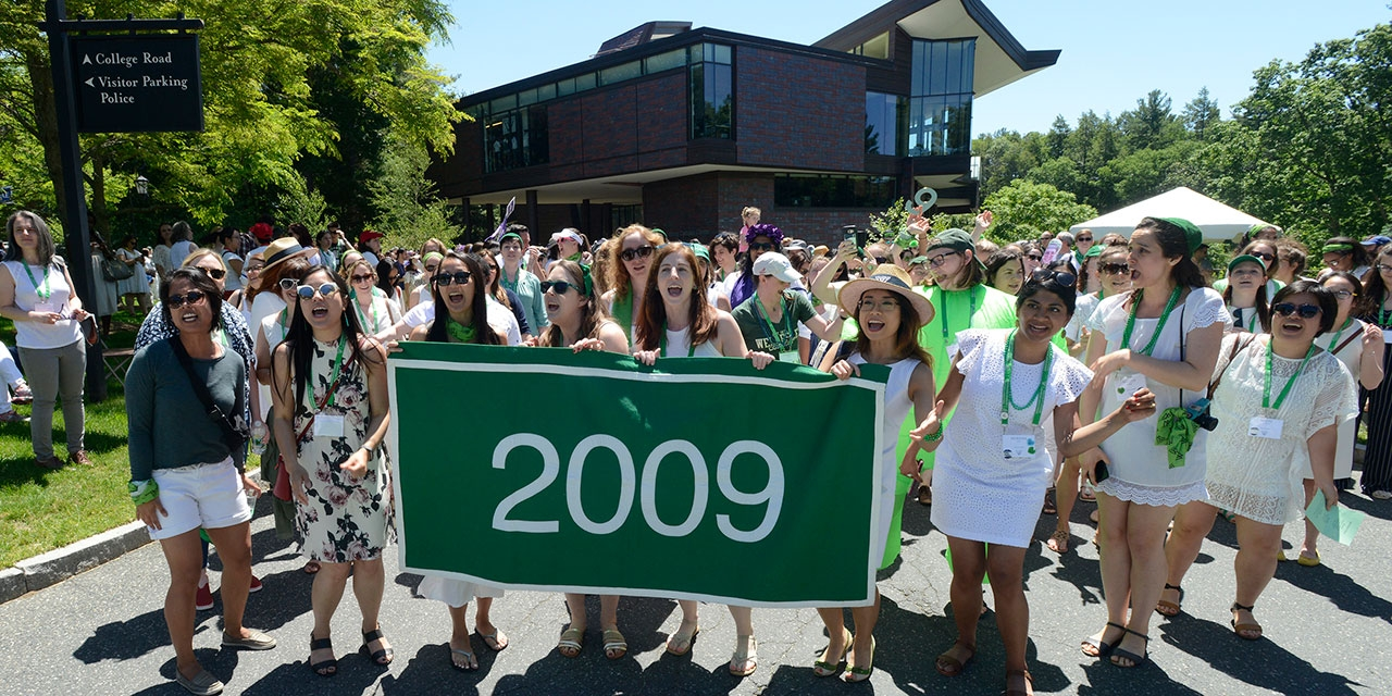 Members of the green class of 2009 stand behind their class banner in front of LuLu