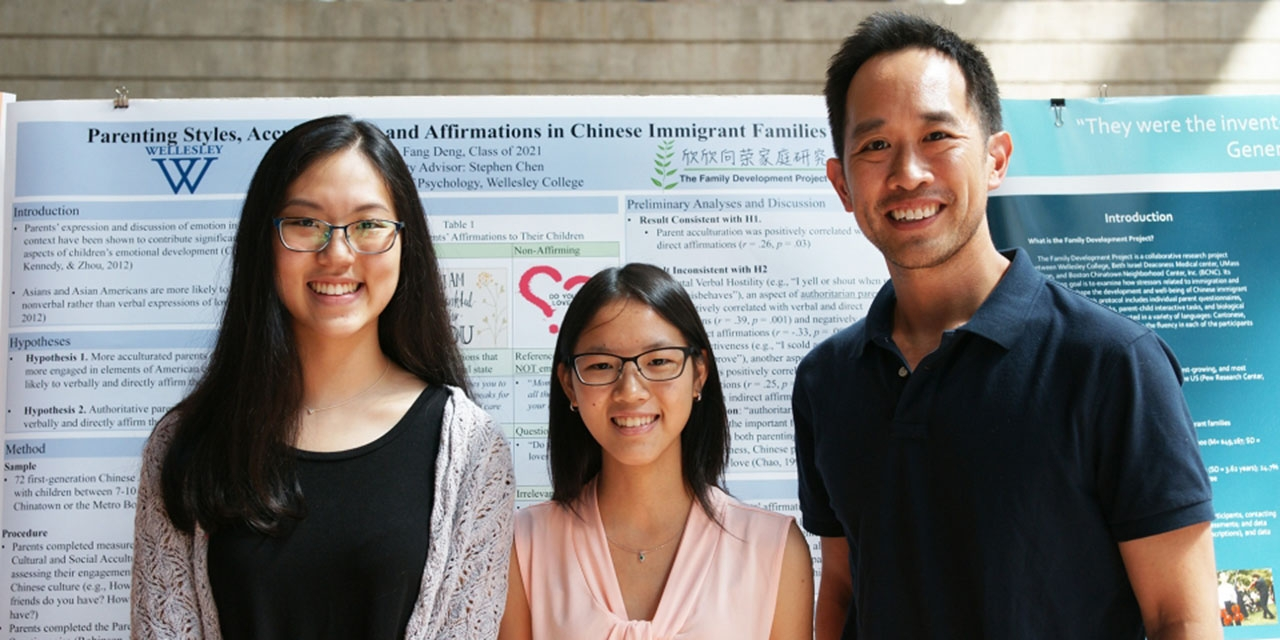 A professor stands in front of a poster with two students. The poster talks about their study.