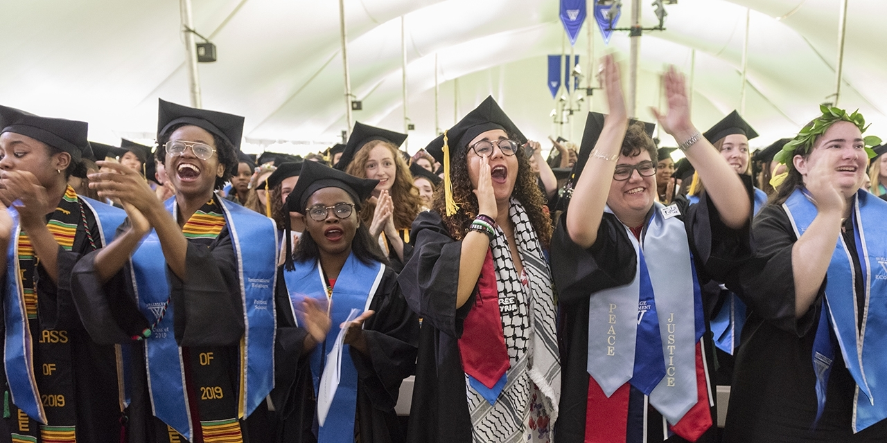 Students cheer under a large tent during commencement 2019
