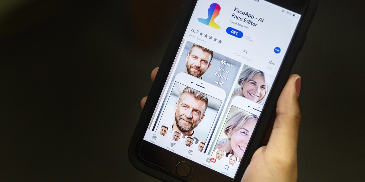 A hand holding a smart phone that displays the FaceApp