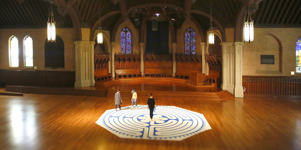 Three women walk a labyrinth inside Houghton Chapel.