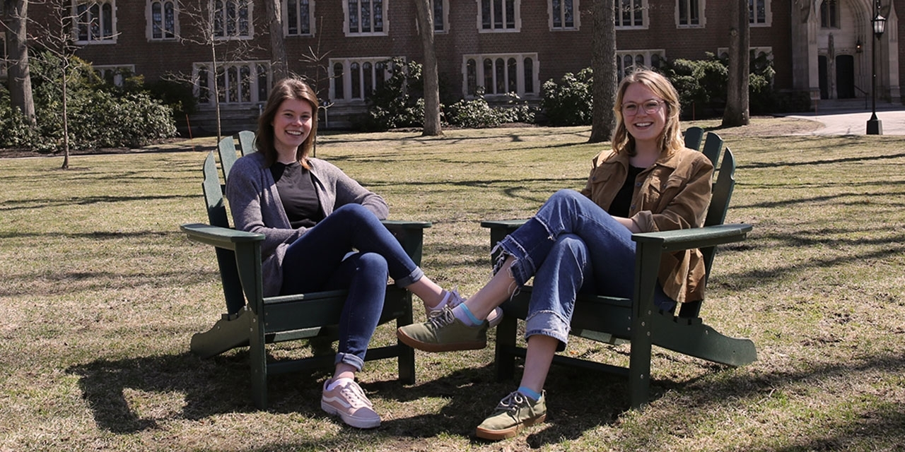 Two students sit in chairs on the academic quad