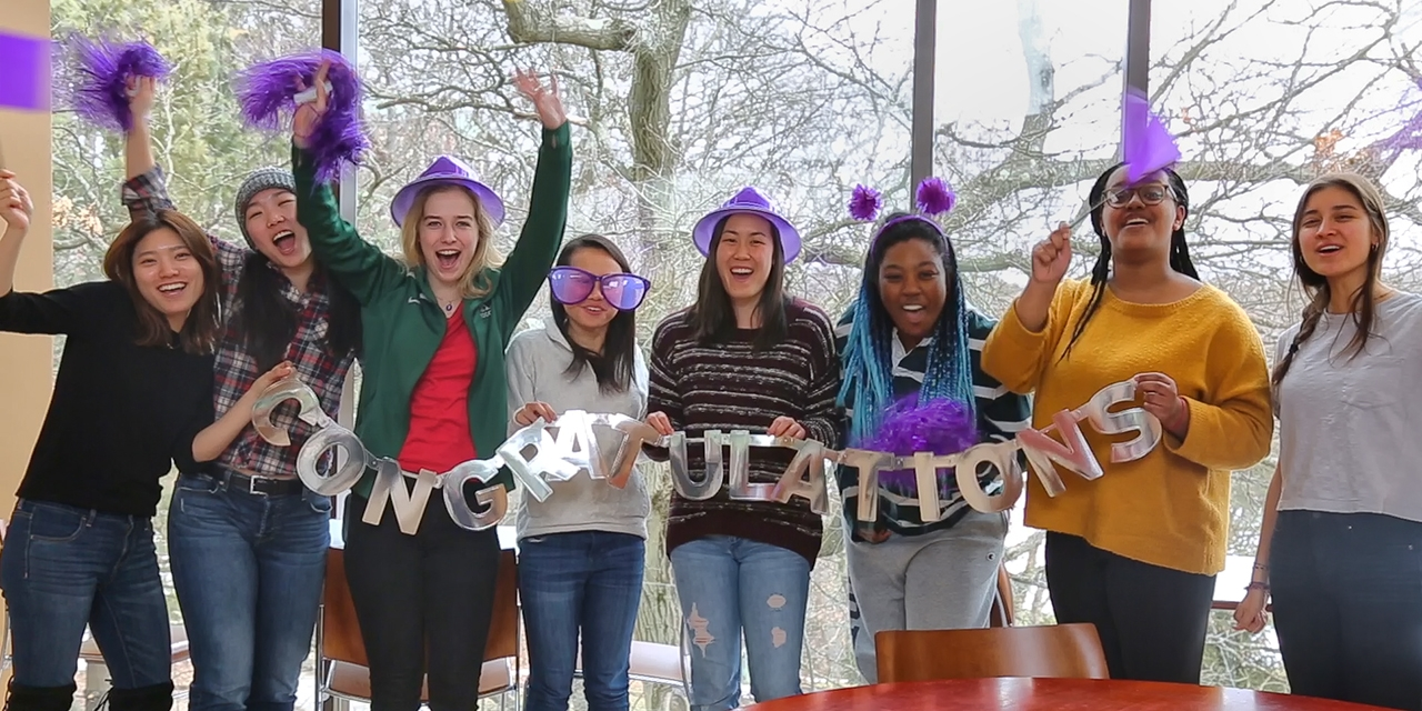 A group of Wellesley students wearing purple gear welcome the Wellesley Class of 2022.