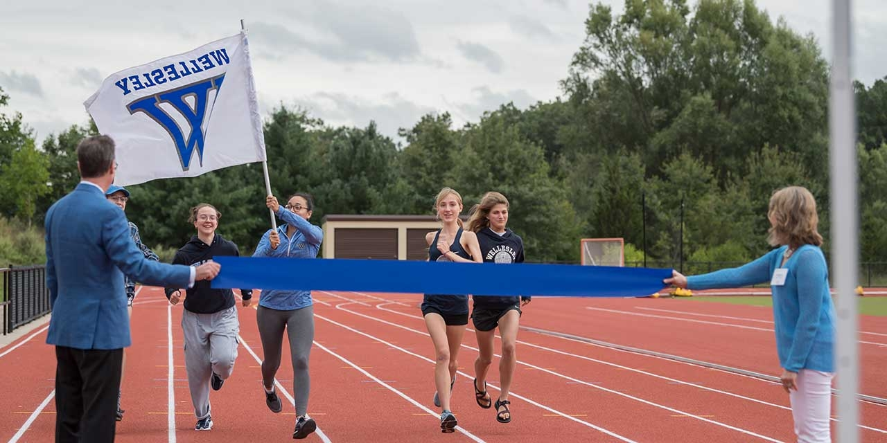 Students run on the track for the first time while carrying a Wellesley flag.