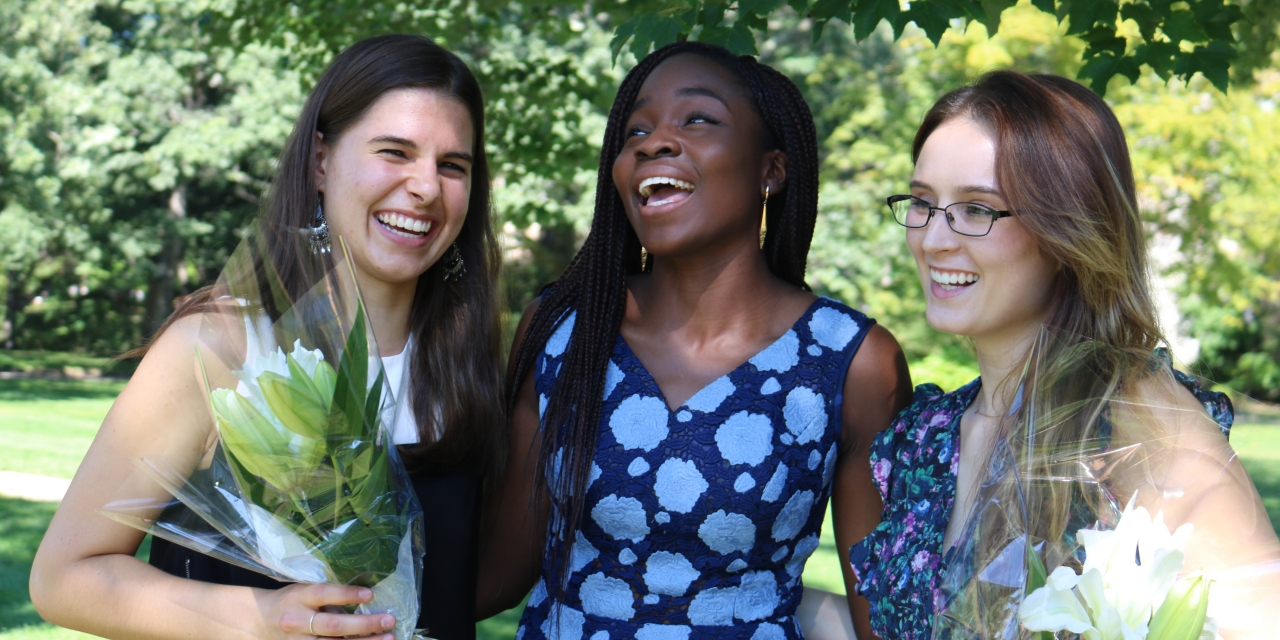Three students laugh together on Flower Sunday.