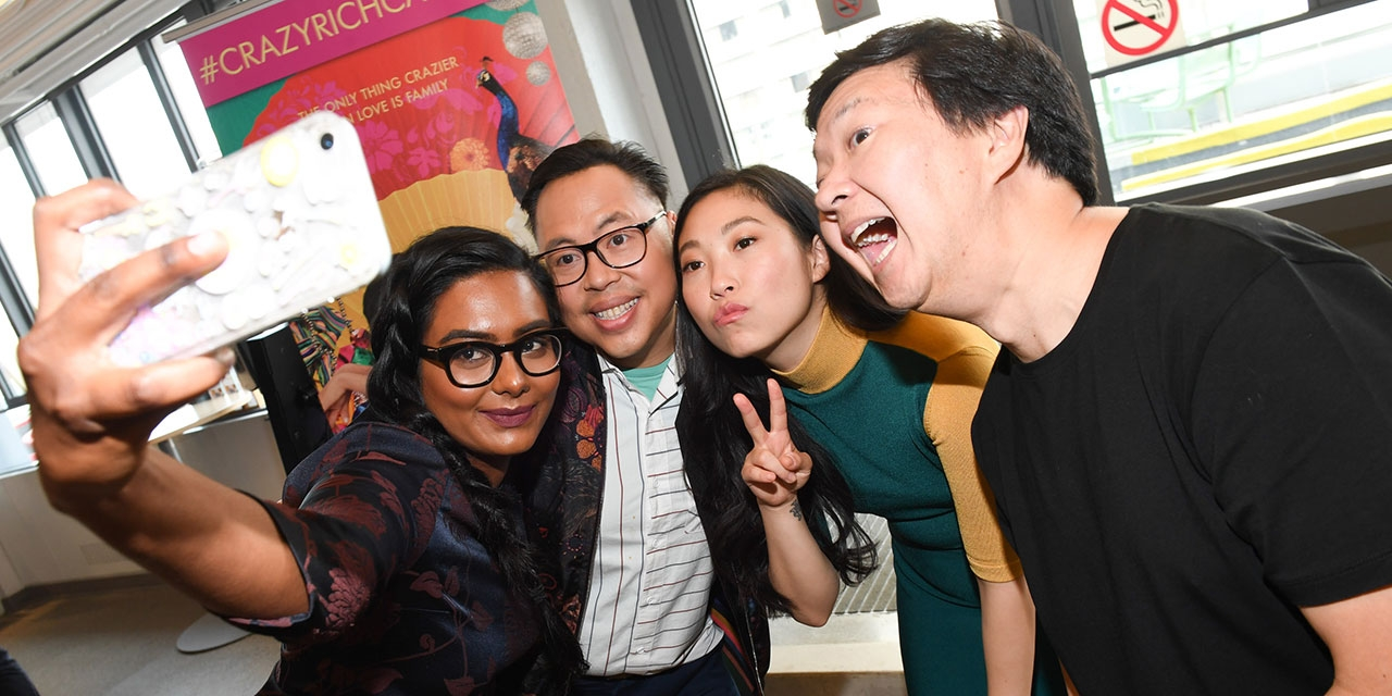 The cast and crew of Crazy Rich Asians take a photo with a fan.