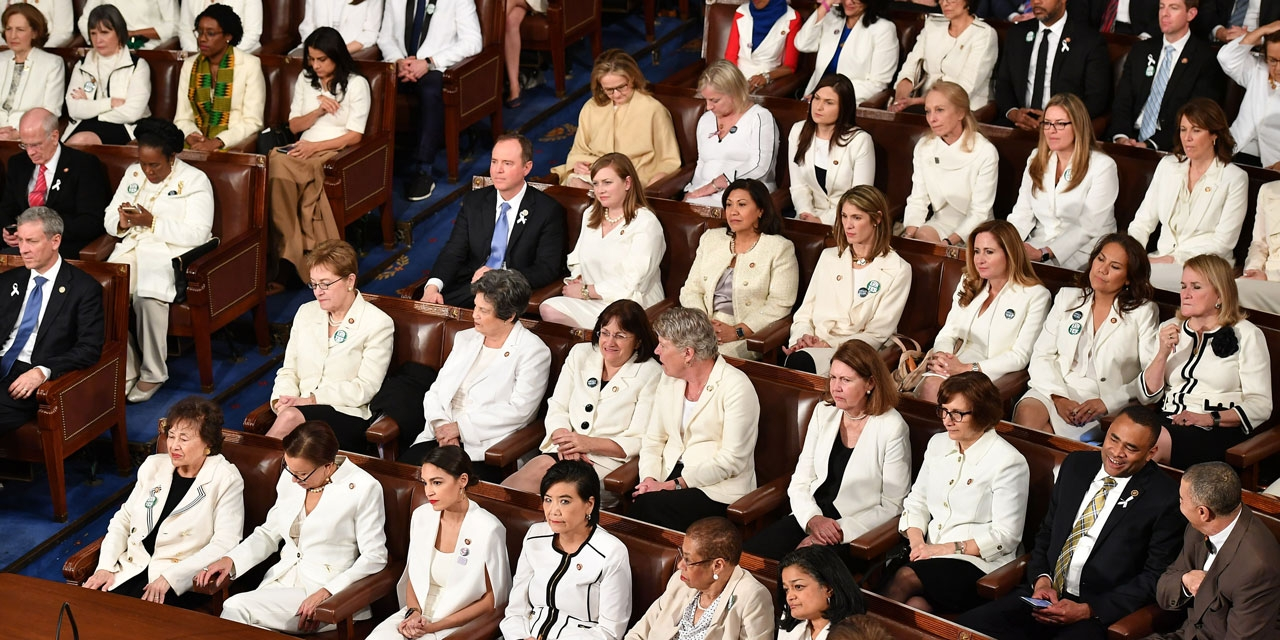 Women members of congress sit wearing white.