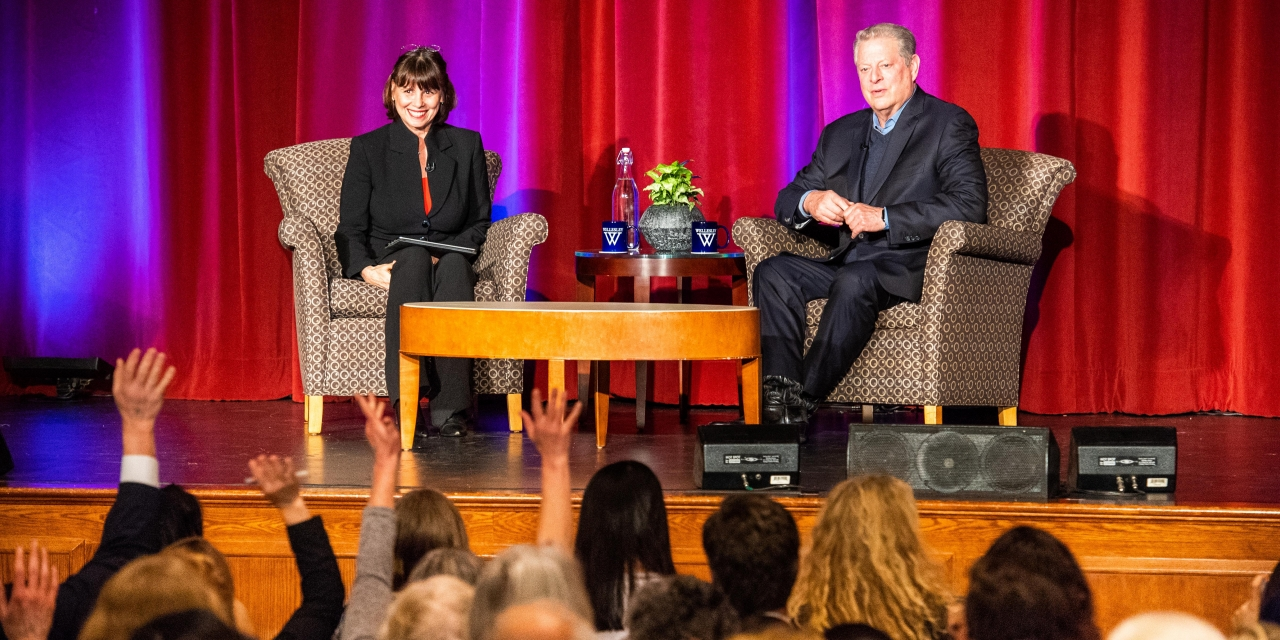 Al Gore and Sue Wagner speak in front of a crowded alumnae ballroom.