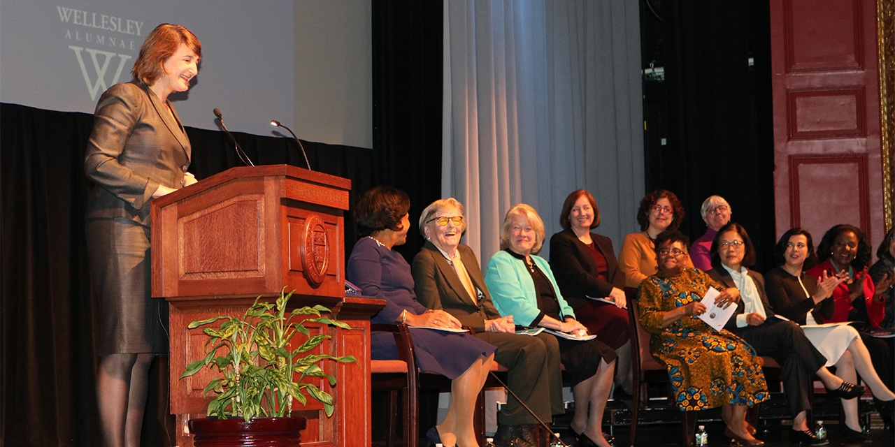 In Alumnae Auditorium, a woman stands at a podium and speaks into a microphone while a group of women sit on stage listening.