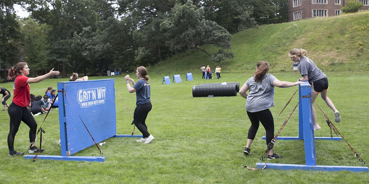 Students jump over obstacles on Severance Green.