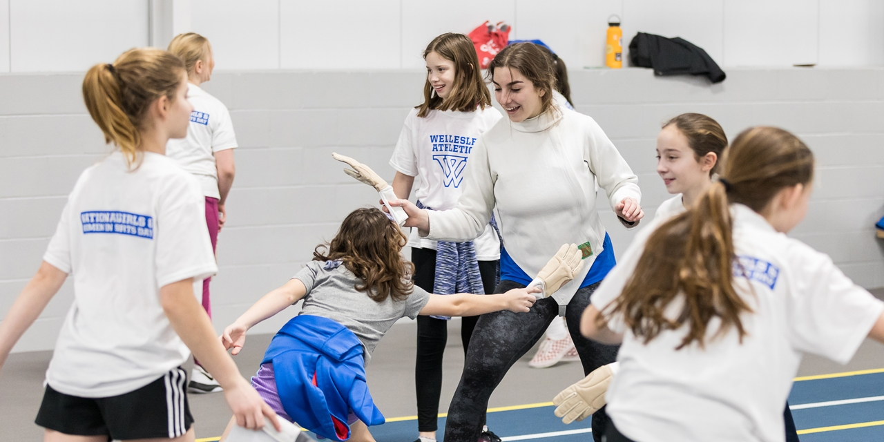 young girls practice fencing technique with gloves