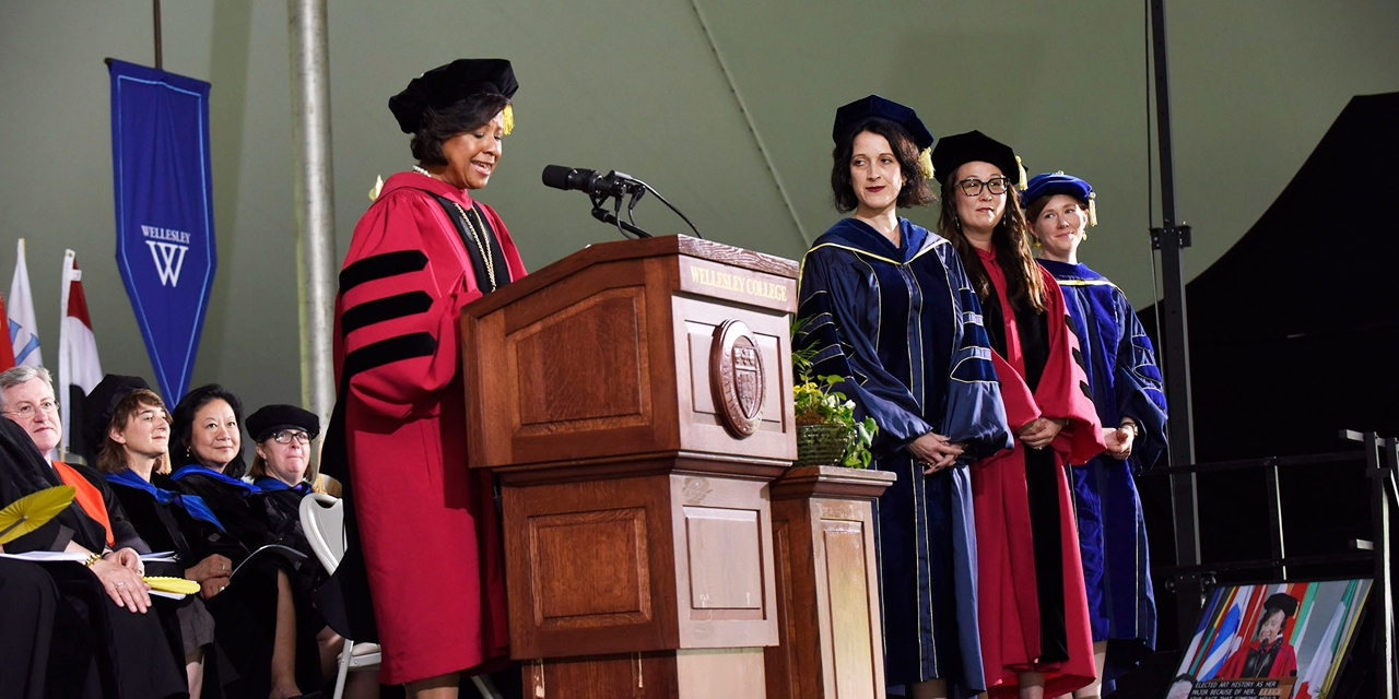 Three professors stand on a stage while the president presents them with an award.