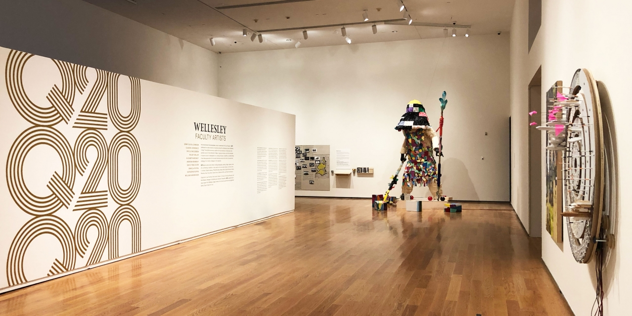 In the Davis Museum. a figure like sculpture stands in a corner.