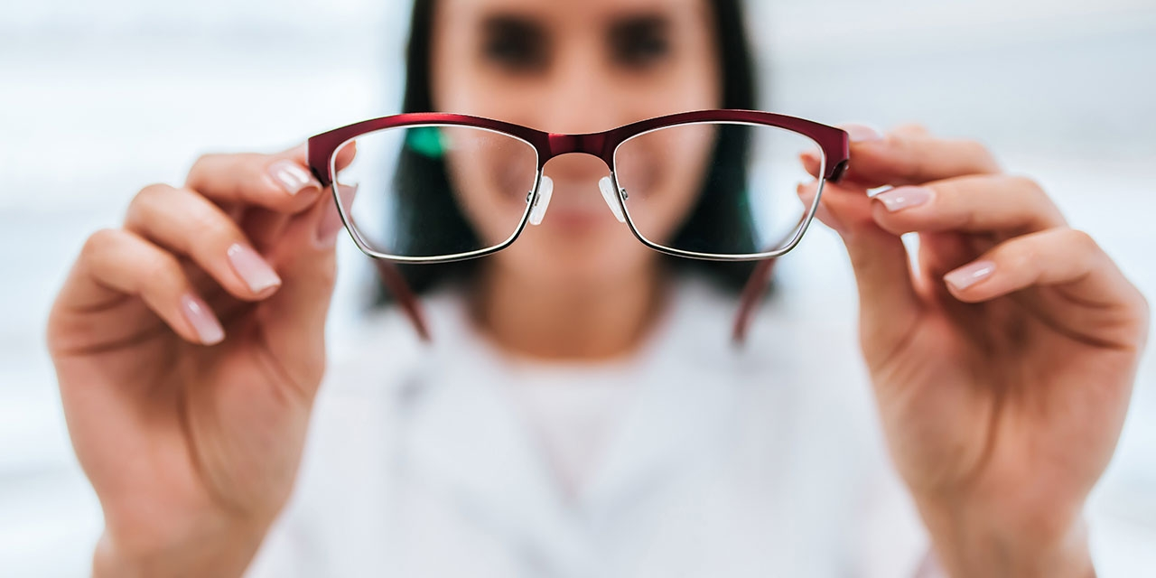 A woman holds eye glasses.