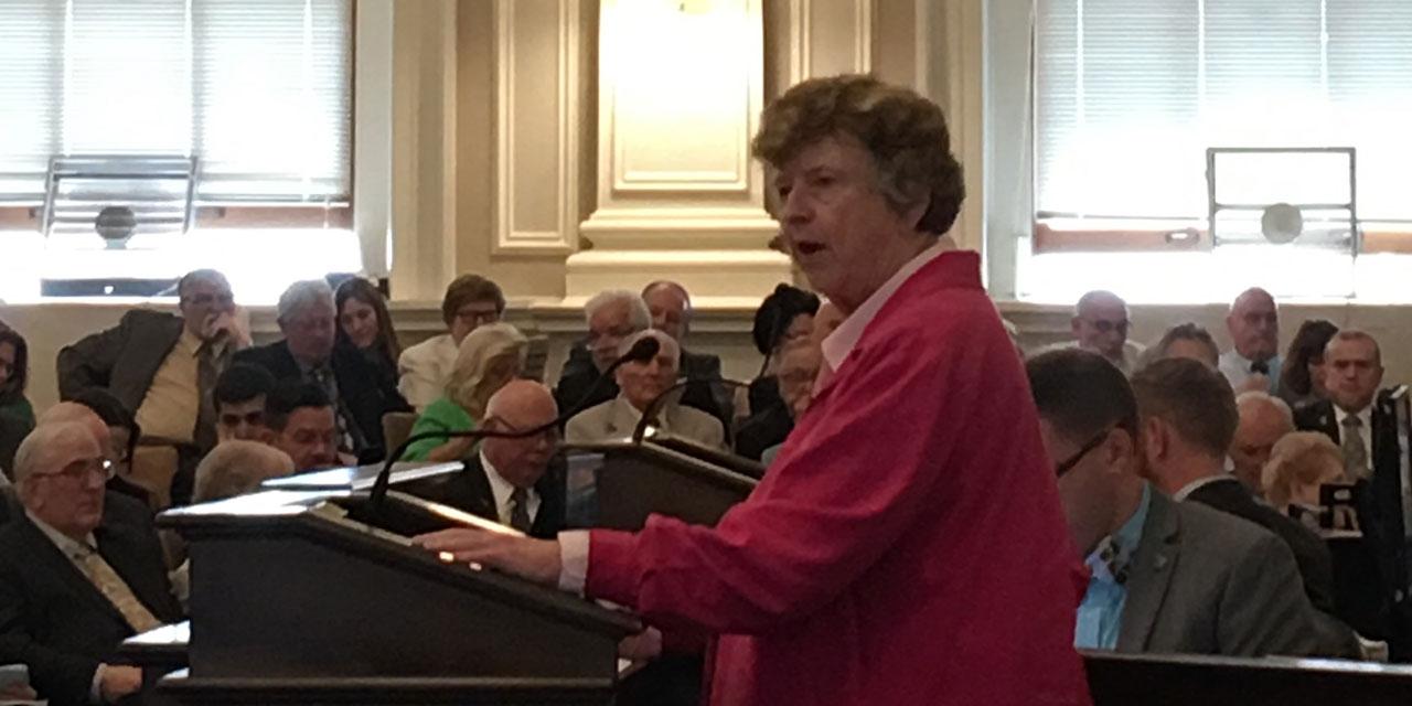 Edith Tucker speaks at a podium.