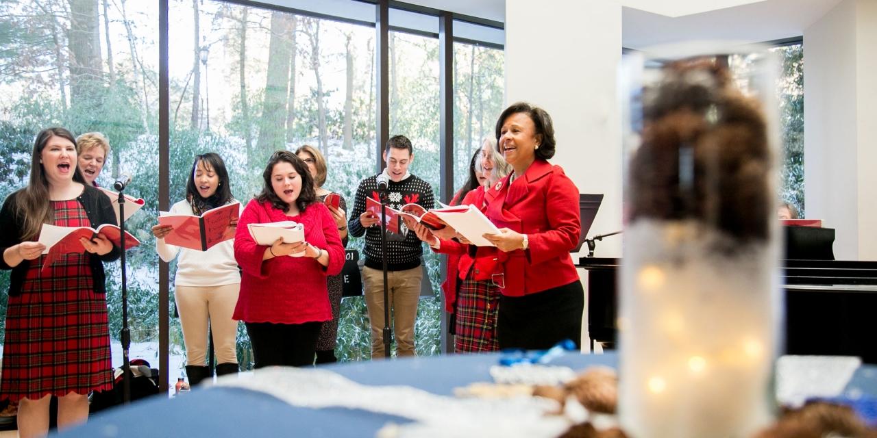 A staff choir sings with President Johnson