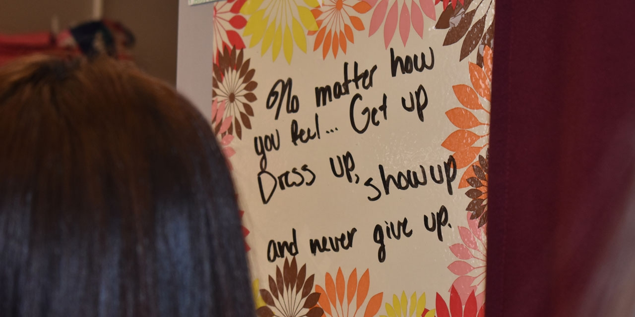 "A student looks at a sign on a wall that reads, ""No matter how you feel, get up, dress up, show up, and never give up."""