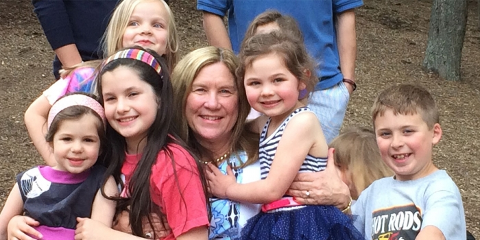 Mary Kloppenberg is hugged by preschool students, she retired after 27 Years as Executive Director of the Wellesley College Children's Center