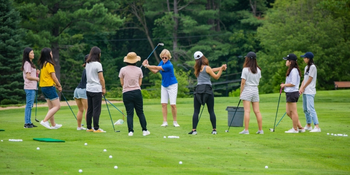Leslie Andrews '82, director of the Nehoiden Golf Club, leads a golf lesson with undergraduate students in a summer program.