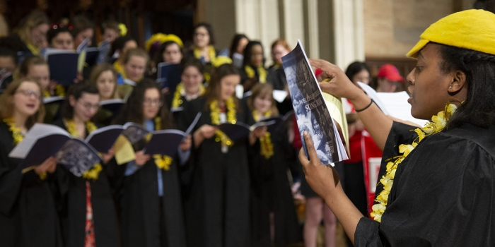 Students dressed in yellow sing inside the chapel