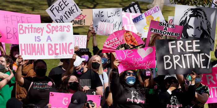 Britney Spears fans hold signs outside a Los Angeles court hearing concerning the pop singer's conservatorship on March 17, 2021