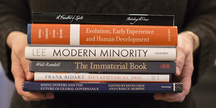 hands holding stack of books