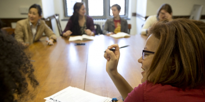 A group os students sit around a large, wooden table, talking to one another in a Calderwood Seminar.
