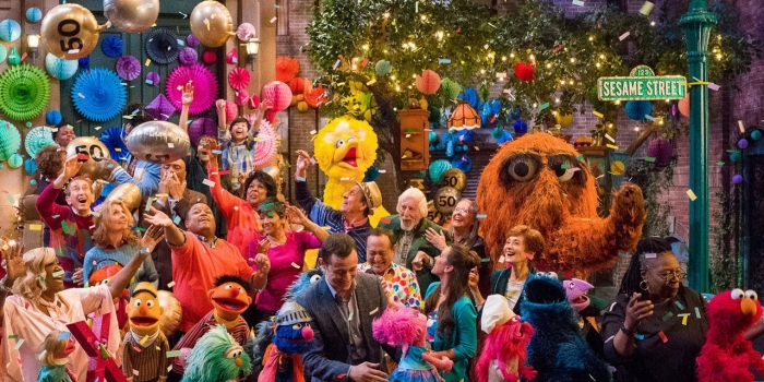 The cast of Sesame Street celebrates on a street corner.