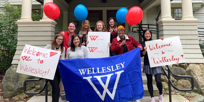 A group of students and admissions officers stand outside the admissions building with signs and balloons.