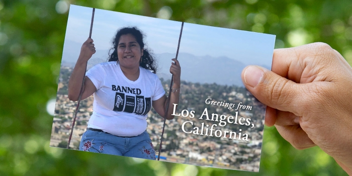 On a postcard, a student sits on a swing that overlooks Los Angeles.